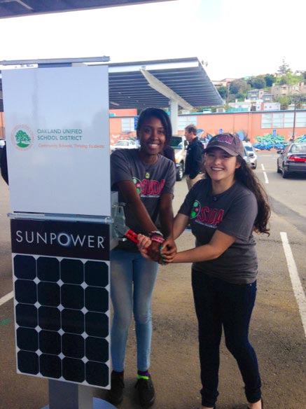 Students Ronye Cooper and Sandra Vivian-Calderon excitedly flip the big switch at the OUSD solar dedication ceremony. (Photo by Renee Solari.)