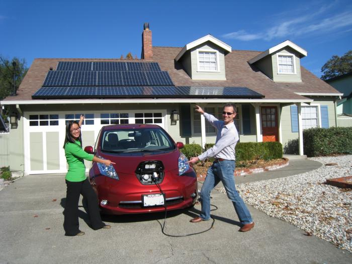Mark and Cathleen Albers with their electric car and SunPower solar system.